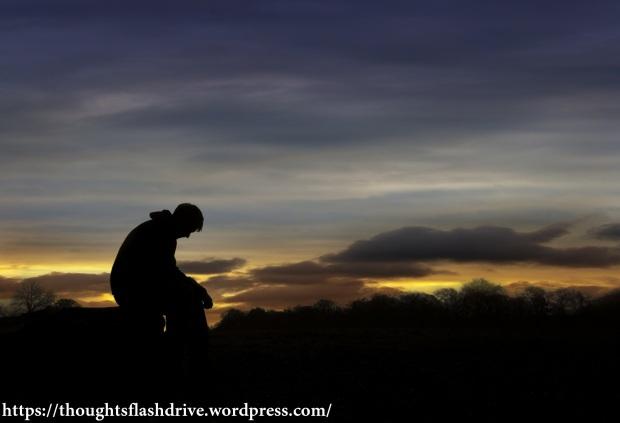 Sad man sitting in sunset